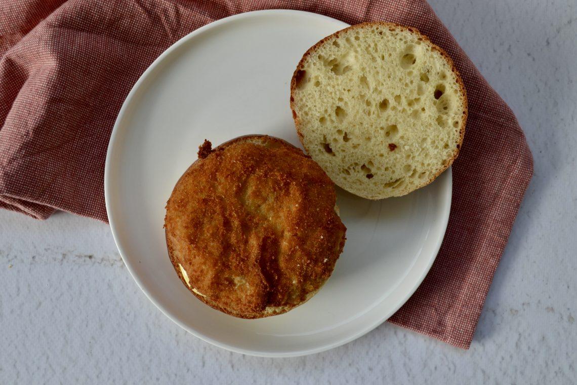 Het broodje met de kroketburger, met de bovenkant naast het broodje