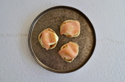 Een foto van een bord met drie blini''s belegd met gerookte zalm