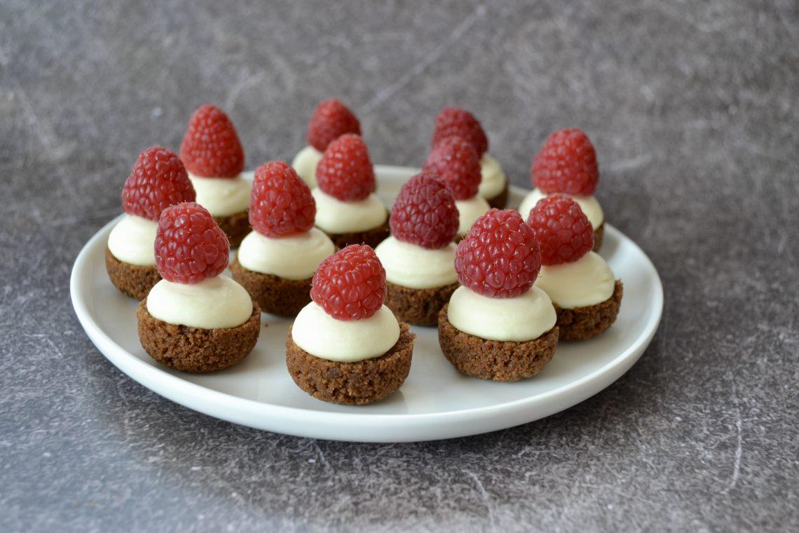 Rond bord met cheesecake bites en een framboos bovenop
