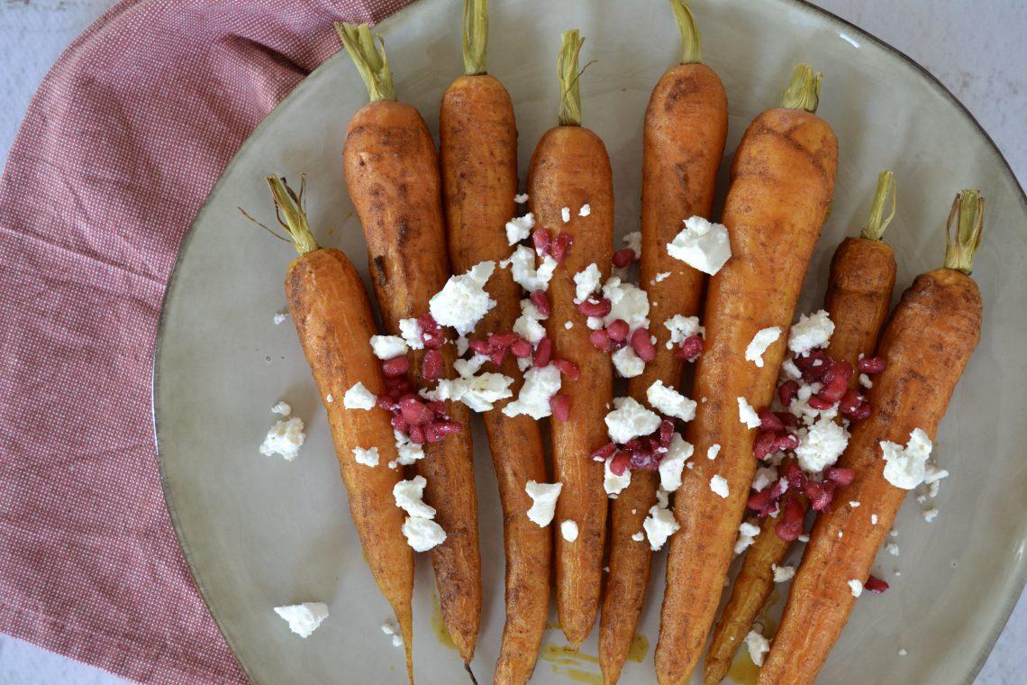 Bovenaanzicht van de geroosterde wortels, met verkruimelde feta en granaatappelpitten