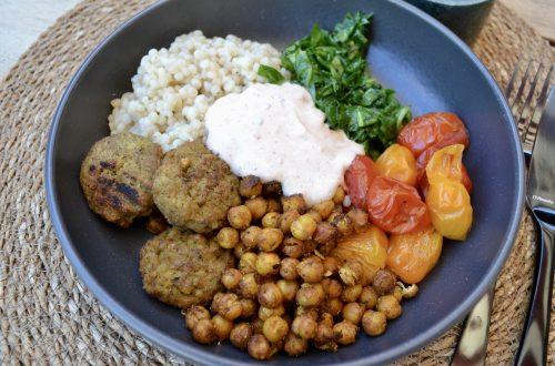 Diep bord gevuld met parelcouscous, gepofte tomaatjes en falafel
