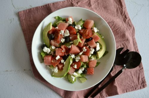 Een foto van een diep bord met watermeloen salade en opschepbestek.