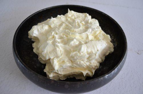 Een diep bord gevuld met Swiss meringue botercrème
